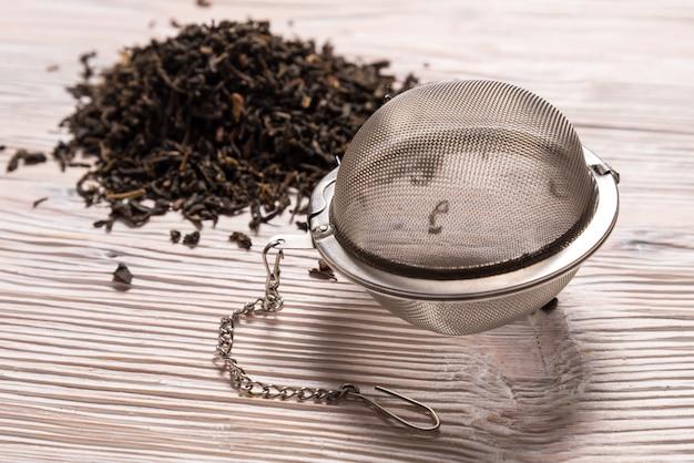 Chá preto com infusor de chá de bola de malha de aço no fundo de madeira Foto Premium
