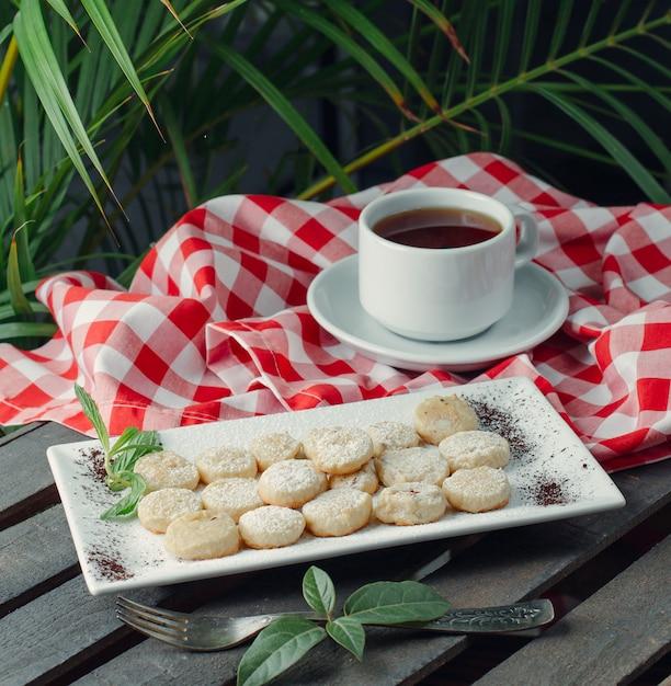 Chá preto servido com travessa de biscoitos pequenos redondos com açúcar em pó Foto gratuita