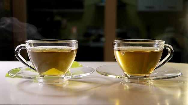 Chá quente com fumaça no copo de vidro com pires. conceito de alimentos e bebidas. Foto Premium