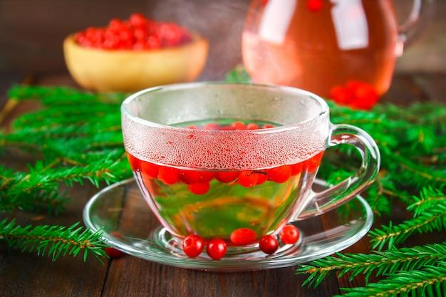 Chá quente de cranberries em um copo de vidro, rodeado por ramos de abeto em uma mesa de madeira. Foto Premium