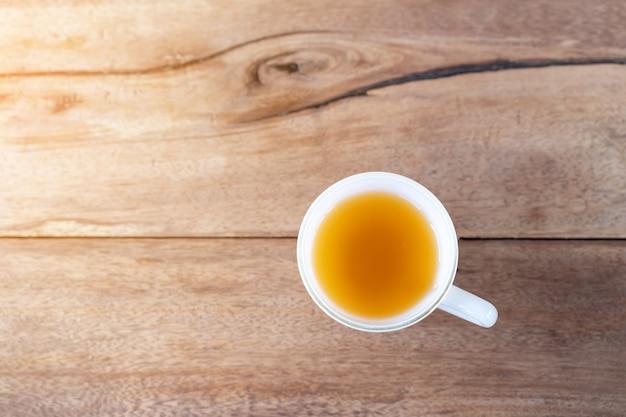 Chá quente em um copo no fundo da mesa de madeira com espaço de cópia Foto gratuita