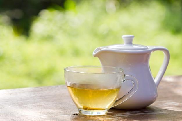 Chá quente ou uma xícara de chá e a tigela de chá branco na mesa de madeira com espaço para refrescos Foto Premium