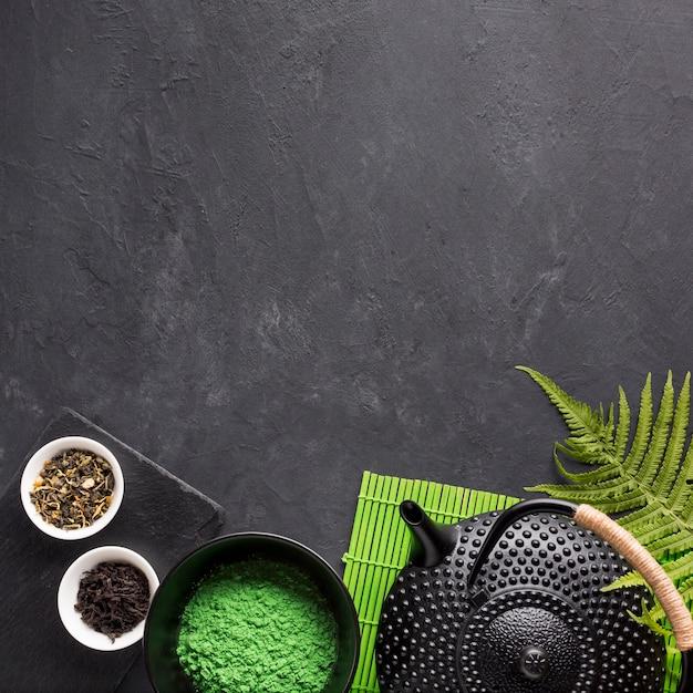 Chá seco erva e chá verde matcha em pó com bule em plano de fundo texturizado preto Foto gratuita