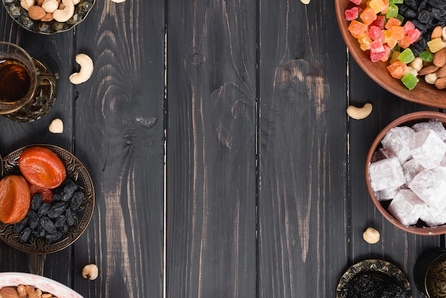 Chá turco; frutas secas; passas de uva; nozes e lukum na mesa de madeira texturizada preta Foto gratuita