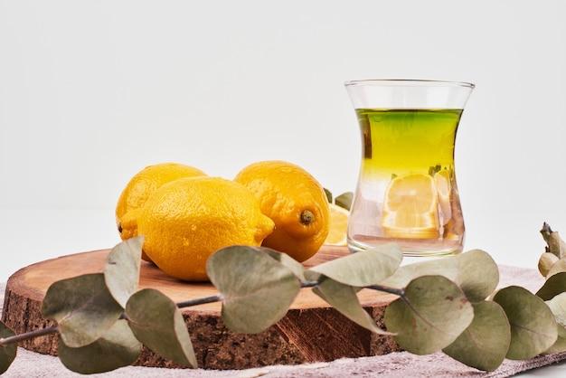 Chá verde com três limões na superfície branca com folhas. Foto gratuita