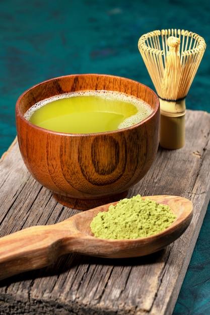 Chá verde do matcha no copo de madeira no fundo esmeralda. Foto Premium