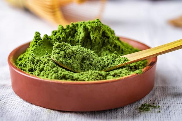 Chá verde em pó com folha em prato de cerâmica em cima da mesa, batedor de arame japonês feito de bambu para cerimônia de chá macha Foto Premium