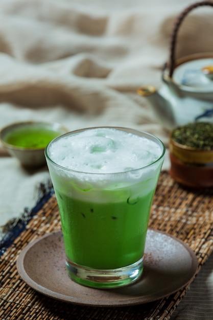 Chá verde gelado em um copo alto com creme coberto com chá verde gelado. decorado com chá verde em pó. Foto gratuita