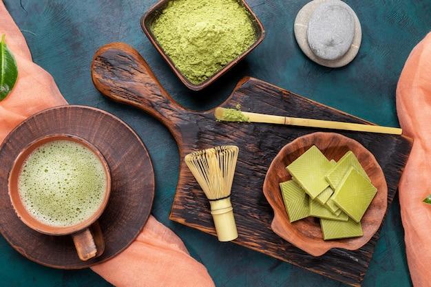 Chá verde matcha, pó e chocolate no fundo esmeralda. vista do topo. Foto Premium