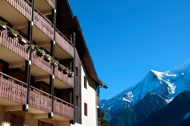 Chalé de esqui alpino europeu tradicional, vista dos alpes à distância. copie o espaço no céu azul. Foto gratuita