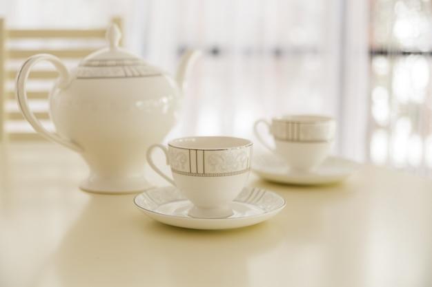 Chaleira branca e duas xícaras de chá na mesa. Foto Premium