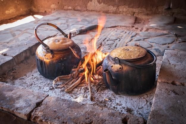 Chaleiras velhas estão fervendo em fogo aberto Foto Premium