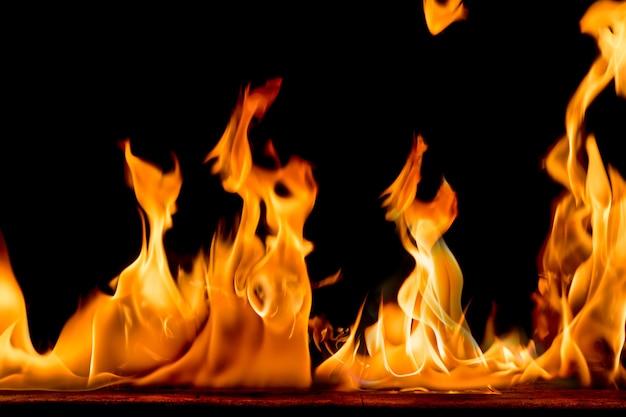 Chamas do fogo no fundo preto. fogo brilhante e colorido contra uma noite preta. Foto Premium