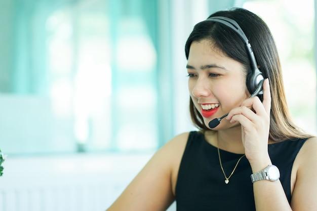 Chame centro mulher trabalhando falando no fone de ouvido tentando responder a resposta ou a trabalhar Foto Premium