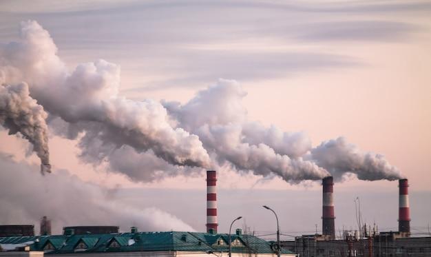 Chaminés industriais com fumaça pesada, causando poluição do ar como um problema ecológico no céu rosa do sol Foto Premium