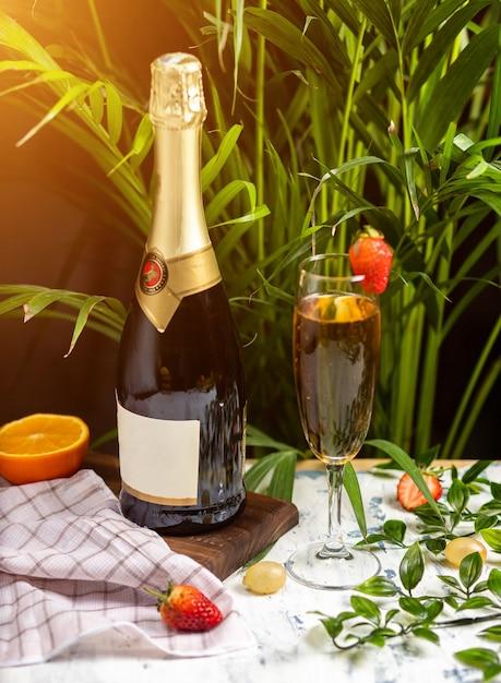 Champagne, prosecco garrafa com dois copos cheios em uma tabela com fruis cítricos e ervas Foto gratuita