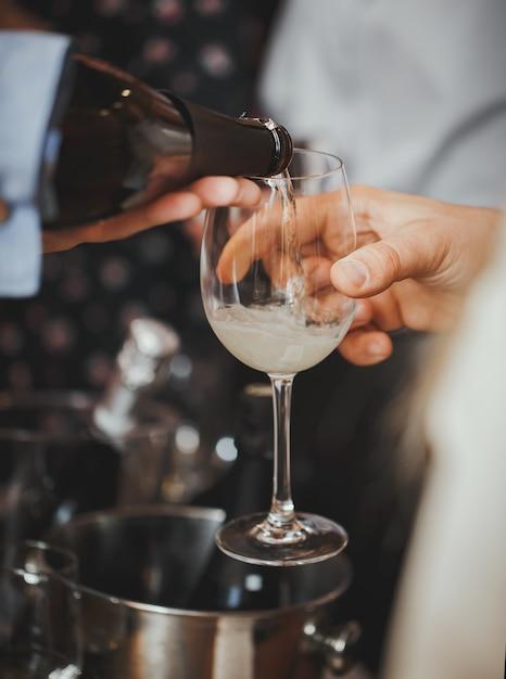 Champanhe é despejado em um copo para o visitante. fechar-se. Foto Premium