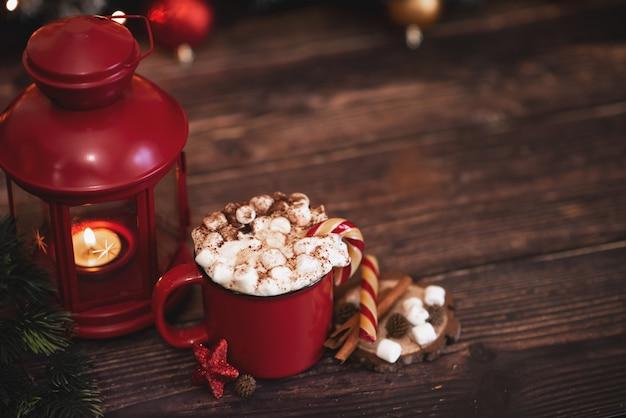 Chantilly de inverno café quente em uma caneca vermelha com biscoitos em forma de estrela e cachecol quente - Foto Premium
