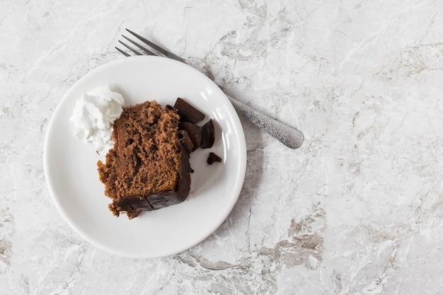Chantilly e fatia de bolo no prato com garfo sobre o balcão de mármore Foto gratuita