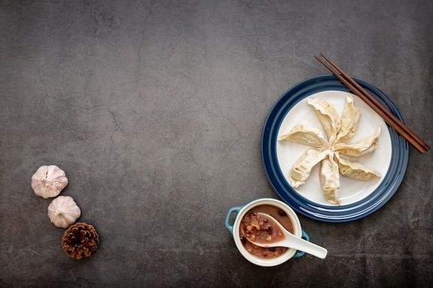 Chapa branca com dim sum e alho em um fundo cinza Foto gratuita