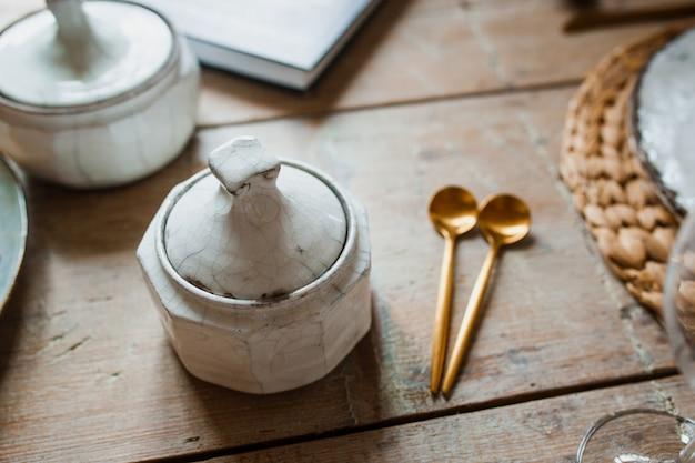 Chapa branca e garfo de ouro com uma colher, aparelhos para fritar, decoração de casamento. jantar de natal ou de ação de tanques. de cima Foto Premium