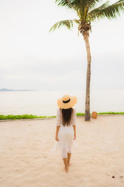 Chapéu bonito asiático do desgaste de mulher do retrato com lazer feliz do sorriso na praia e no mar em férias do feriado Foto gratuita