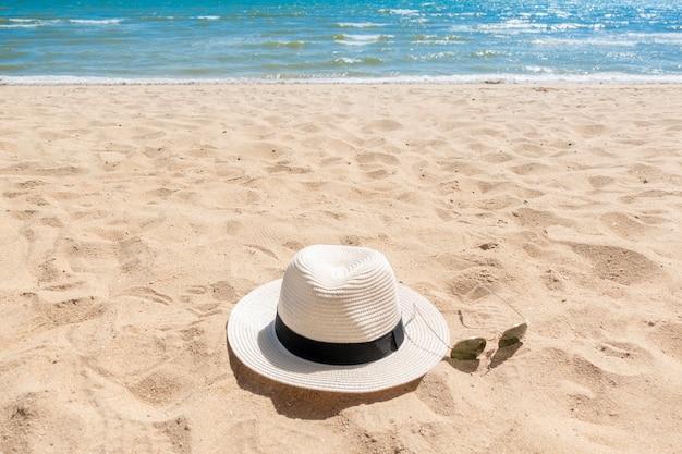Chapéu branco e óculos de sol na praia, conceito de verão Foto Premium