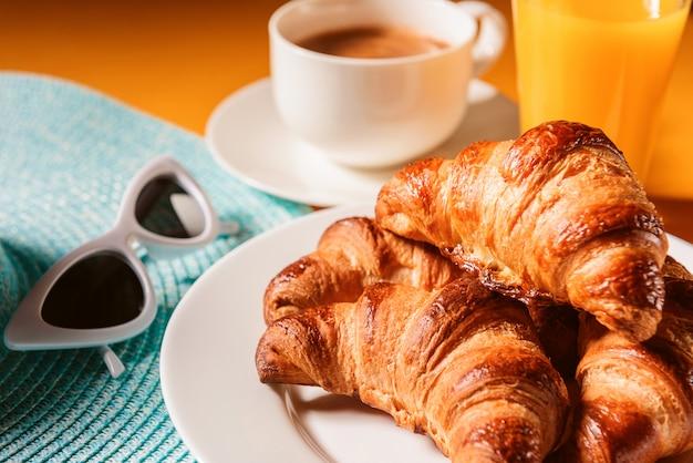 Chapéu, croissant de óculos de sol com uma xícara de café e um copo de suco de laranja em uma mesa amarela ao sol Foto Premium