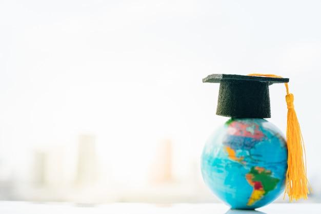 Chapéu da graduação no topo mapa do modelo do globo da terra com fundo da cidade. Foto Premium