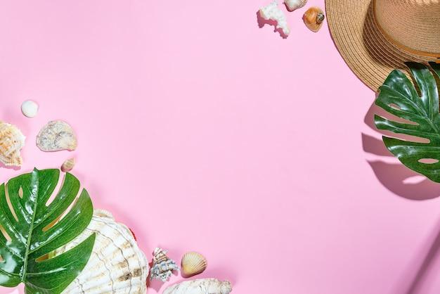 Chapéu de acessórios de praia, folhas de palmeira, chapéu de praia de estrela do mar e concha do mar em fundo de papel rosa Foto Premium