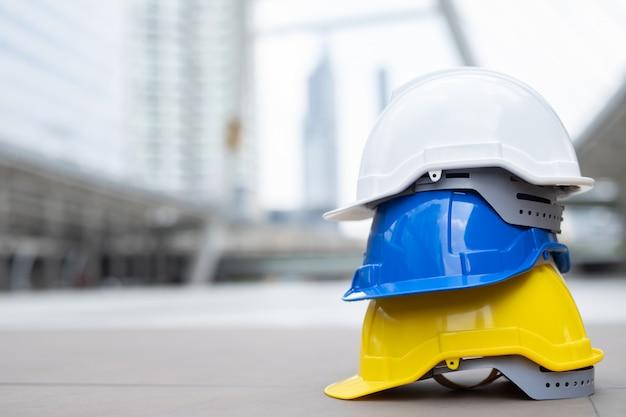 Chapéu de capacete de desgaste de segurança no projeto no canteiro de obras de construção no piso de concreto na cidade. Foto Premium