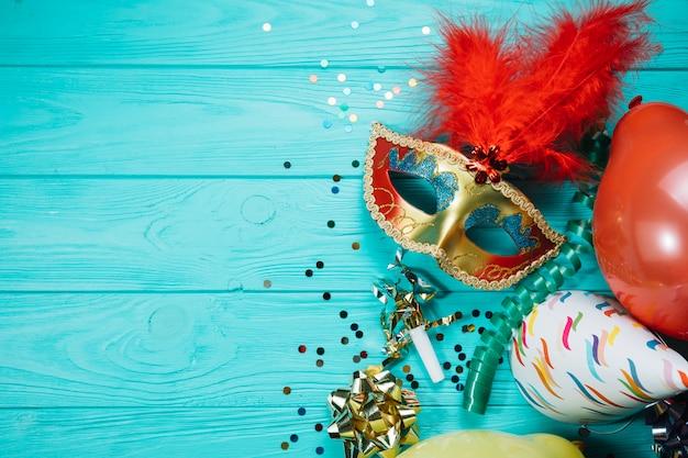 Chapéu de festa; balão com confete e máscara de carnaval de máscaras de ouro na mesa de madeira Foto gratuita