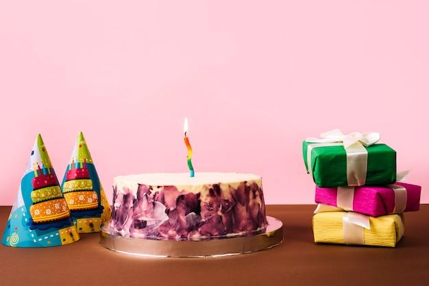 Chapéu de festa; bolo de aniversário e pilha de caixas de presente na mesa contra um fundo rosa Foto gratuita
