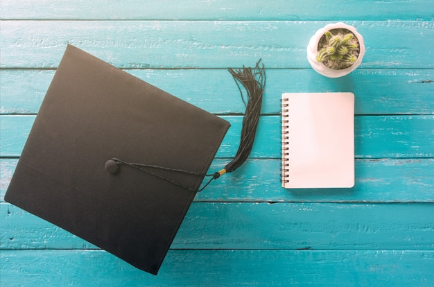 Chapéu de formatura, chapéu na mesa de madeira azul com vista caderno vazio de cima. Foto Premium