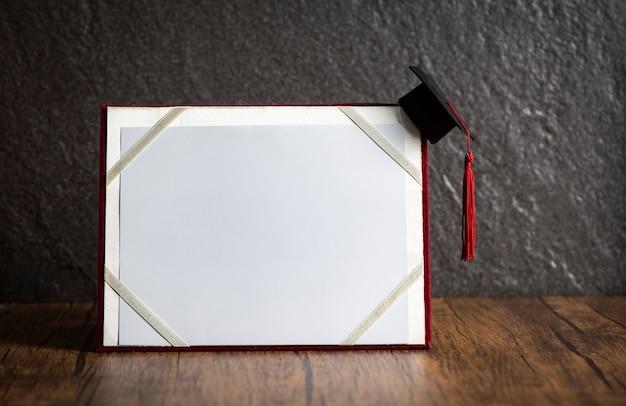 Chapéu de formatura no conceito de educação de certificado de graduação em madeira com fundo escuro Foto Premium