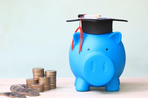 Chapéu de formatura no porquinho e pilha de dinheiro de moedas em branco Foto Premium