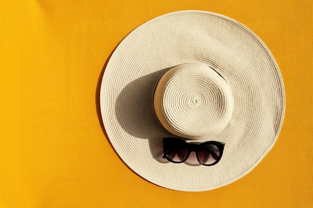 Chapéu de palha bonito com óculos de sol no fundo vívido vibrante amarelo. vista do topo. conceito de férias de viagem de verão. Foto gratuita