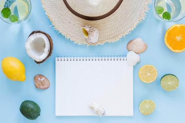Chapéu de palha com frutas exóticas e notebook Foto gratuita