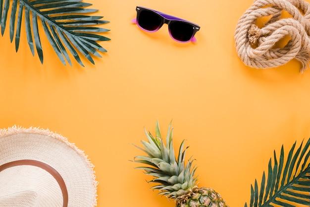 Chapéu de palha com óculos de sol e folhas de palmeira Foto gratuita
