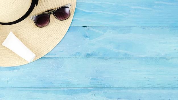 Chapéu de palha com óculos escuros e creme protetor solar Foto gratuita