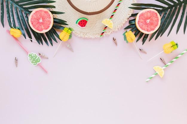 Chapéu de palha com toranja e folhas de palmeira Foto gratuita