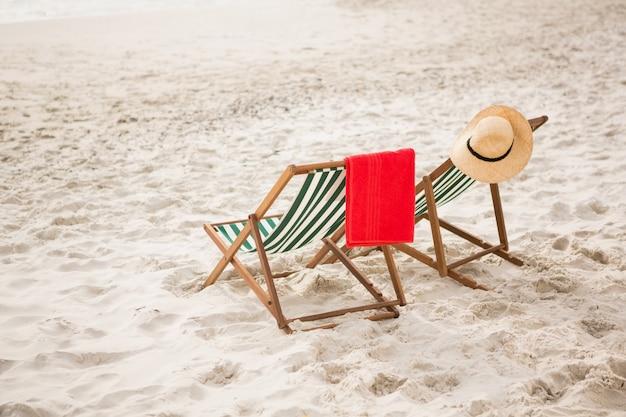 Chapéu de palha e toalha mantidos em cadeiras de praia Foto gratuita