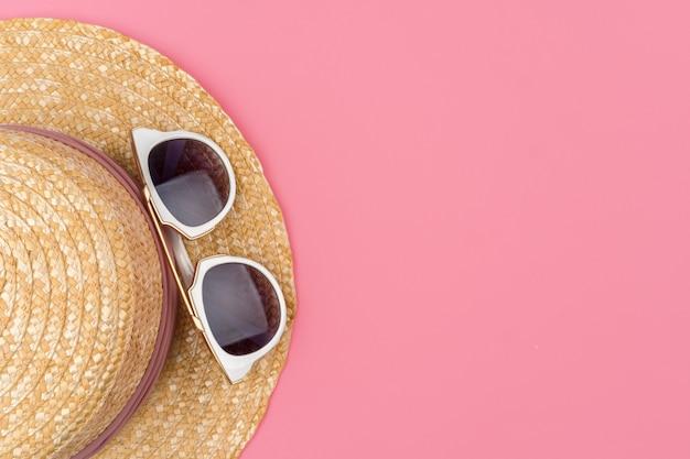 Chapéu de palha feminino e óculos de sol para vista superior de férias de praia Foto Premium
