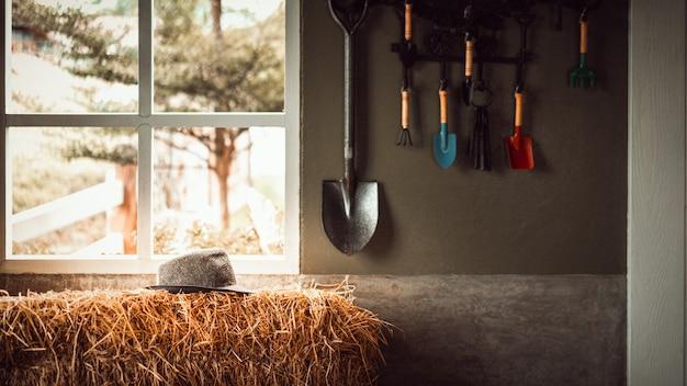 Chapéu de palha na pilha de palha com ferramenta de jardim pendurado na parede do galpão Foto Premium