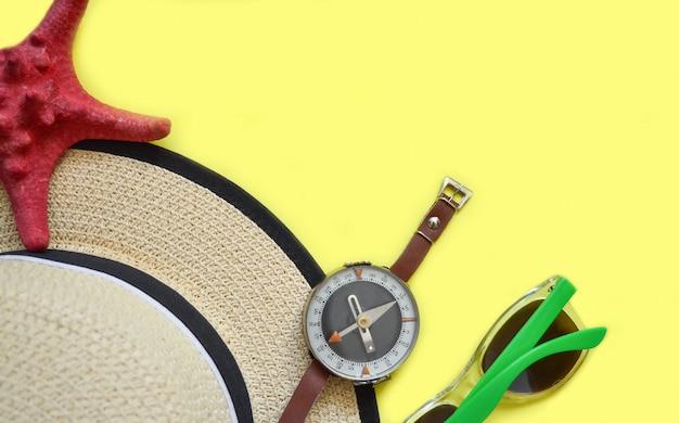 Chapéu de palha, óculos de sol, bússola e estrela do mar em amarelo Foto Premium