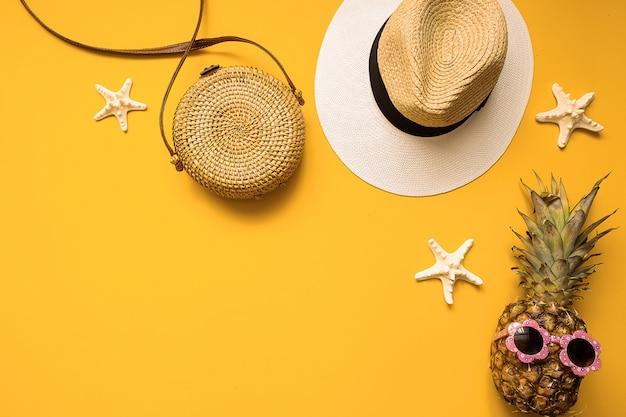 Chapéu de palha, saco de bambu, abacaxi em óculos de sol e estrelas do mar, vista superior Foto Premium