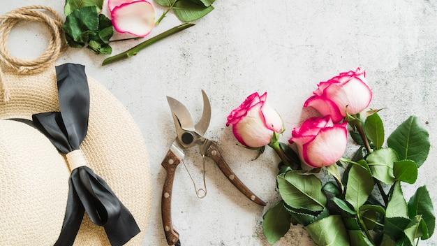 Chapéu de palha; tesouras de podar e galhos de rosas em pano de fundo concreto Foto gratuita