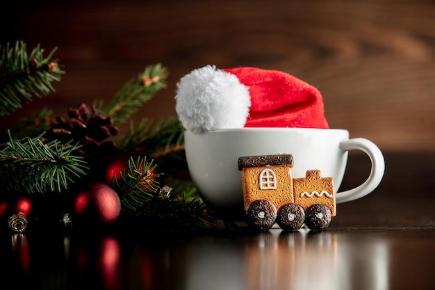 Chapéu de papai noel e copo com biscoito de gengibre Foto Premium