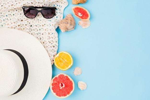 Chapéu de verão e óculos de sol perto de frutas e conchas Foto gratuita