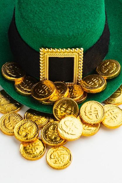 Chapéu e moedas de duende de ângulo alto Foto gratuita